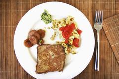 Scrambled egg with tomatoes, sausage and French toast, on a white plate Stock Photos