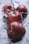 Red apples in water with a jet of water Kuvituskuvat