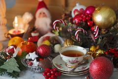 A cup of tea with a rose pattern, Christmas biscuits and Christmas decorations Stock Photos