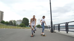 The guy with the girl riding on the promenade in long boards Stock Footage