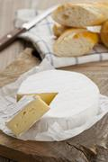 Camembert, one slice cut, on a wooden platter with chunks of baguette Stock Photos