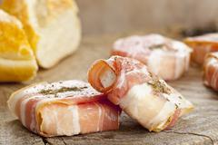 Young goat's cheese wrapped in bacon with herbes de Provence Stock Photos