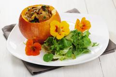 Fried Chantarelles in a Pumpkin wilth Wild Herbs Salad, selective focus Stock Photos