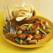 Sweet and sour chicken with baby sweetcorn and prawn crackers Stock Photos