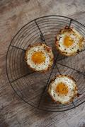 Eggs in baked hash brown nest with goat cheese and arugula filling Stock Photos