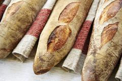 Three baguettes in a row on a linen cloth Stock Photos