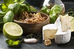 Cheese Camembert, walnuts, fresh basil and lime over dark bakground Stock Photos