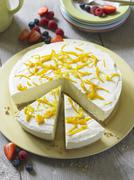 Cheesecake with lemon zest, partly sliced Stock Photos