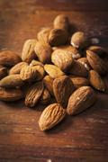 Almonds on a wooden surface Stock Photos