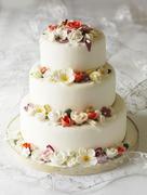 Three-tier wedding cake with fondant flowers Stock Photos