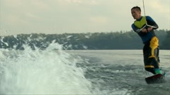 Wakeboarder man riding the wave, making tricks and jump the water Stock Footage