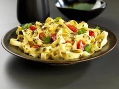 Tagliatelle with coriander and chili pasta sauce and tomatoes Stock Photos