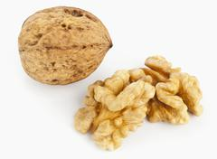 A whole walnut in its shell and two walnut halves Stock Photos