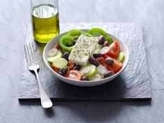 A Greek salad next to a bottle of olive oil Kuvituskuvat