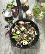Fried mushrooms with red onions, spring onions, thyme marjoram and olive oil Stock Photos