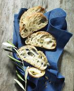 Slices of olive ciabatta on a cloth with an olive sprig Stock Photos