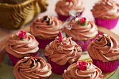Cupcakes decorated with pink buttercream icing with a blown out, smoking candle Stock Photos