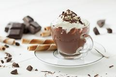 A cup of hot chocolate topped with cream and grated chocolate along with broken Stock Photos