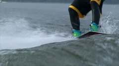 Tilt up shot man in diving suit wake boarding behind the speed boat in water Stock Footage