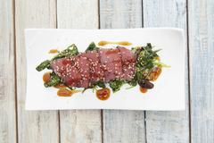 Tuna sashimi with sesame on a bed of seaweed Stock Photos