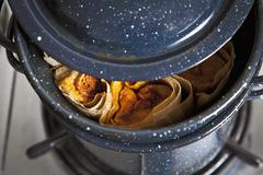 Chicken tamales steaming in a pot Stock Photos