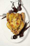 Roast chicken with roast beetroot (seen from above) Stock Photos