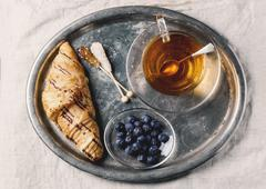 A cup of tea, croissants and blueberries on an old-fashioned tray Stock Photos