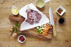 Raw pork cheeks with ingredients on a wooden table Stock Photos
