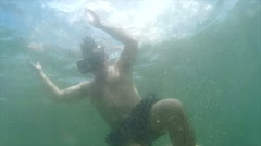 Wide shot VR headset wearing man descends under ocean waves Stock Footage