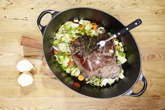 Leg of venison with rosemary, onions, leeks and carrots in a braising dish Stock Photos