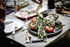 Artichokes, rosemary and tomatoes on a wooden board Stock Photos