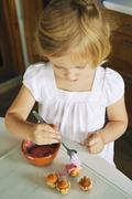 A little girl decorating mini muffins in a kitchen Stock Photos