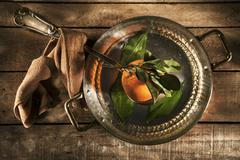 A freshly picked orange in a copper saucepan Stock Photos