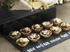 Brie and red onion tartlets Stock Photos