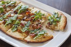 A pizza topped with bacon, gorgonzola and rocket Stock Photos