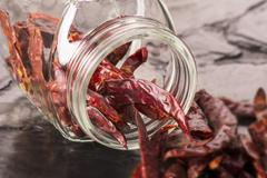 Dried chilli peppers spilling from an overturned storage jar Stock Photos