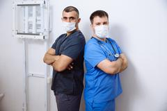 Two surgeons in sterile uniforms standing back to  with arms folded and looking Stock Photos