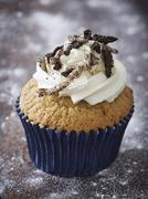 A cupcake topped with buttercream and chocolate biscuits Stock Photos