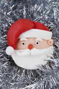 A Father Christmas cupcake on silver tinsel Stock Photos