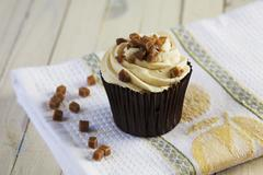 A caramel cupcake decorated with toffee pieces Stock Photos
