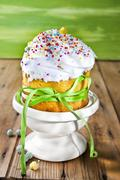 A cupcake decorated with buttercream, sugar sprinkles and a green bow Stock Photos