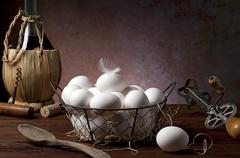 Fresh eggs in a wire basket next to antique kitchen utensils and a bottle of Stock Photos
