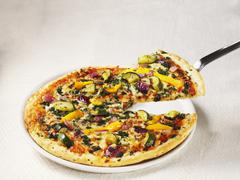 A pizza topped with Mediterranean vegetables Stock Photos
