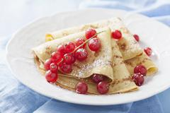 Pancakes with redcurrants and icing sugar Stock Photos