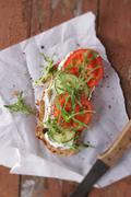 A slice of bread topped with cream cheese, cucumber, tomato and rocket Kuvituskuvat