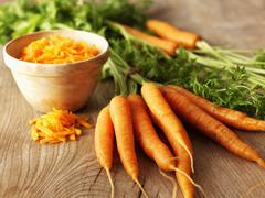 Whole organic carrots and a bowl of grated carrot Stock Photos