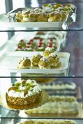 Various cakes and pastries in a refrigerated display cabinet Stock Photos