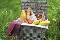 A picnic basket filled with fruit, rolls and orange juice Stock Photos