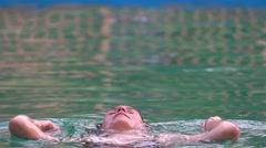 Beautiful girl in a white bikini swimming in the pool under water stream and Stock Footage
