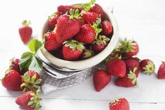 Fresh strawberries in a bowl and next to it Stock Photos